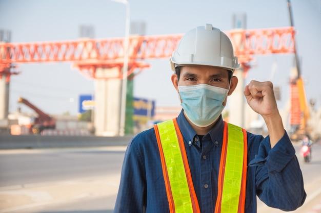 Ingenieur dragen gezichtsmasker werken aan de aanleg van wegen op de site