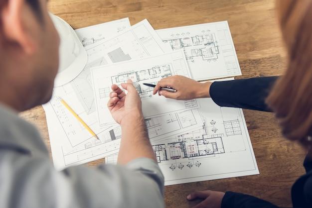 Ingenieur en architect bespreken over blauwdruk lay-outontwerp van elektriciteitsplan
