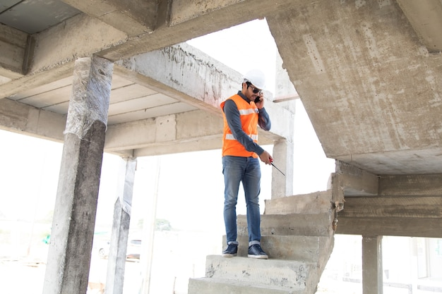 Ingenieur en architect werken bij bouwplaats met blauw opdruk. spaanse elektricien werkt en kijkt blauwdruk in nieuwe huis bouwplaats.