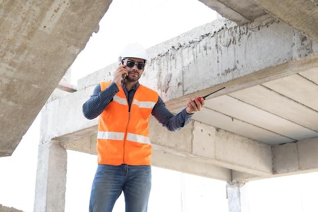 Ingenieur en architect werken bij bouwplaats met blauw opdruk.