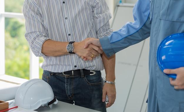 Ingenieur en architecten handen schudden overeenkomst toe te treden om te werken op de werkplek