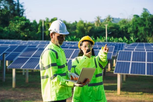 Ingenieur en technicus die apparatuur in zonnepanelen controleert.