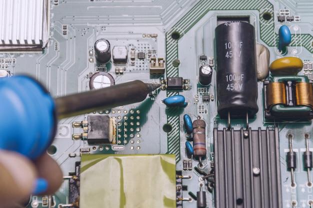 Ingenieur gebruik soldeerbout om televisiebord te repareren