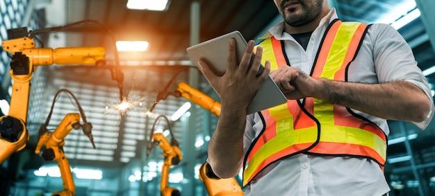 Ingenieur gebruikt geavanceerde robotsoftware om de robotarm van de industrie in de fabriek te besturen