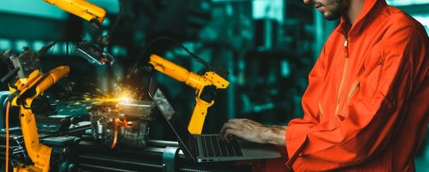 Ingenieur gebruikt geavanceerde robotsoftware om de robotarm van de industrie in de fabriek te besturen; Premium Foto