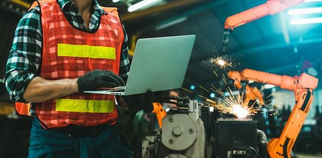 Ingenieur gebruikt geavanceerde robotsoftware om de robotarm van de industrie in de fabriek te besturen;
