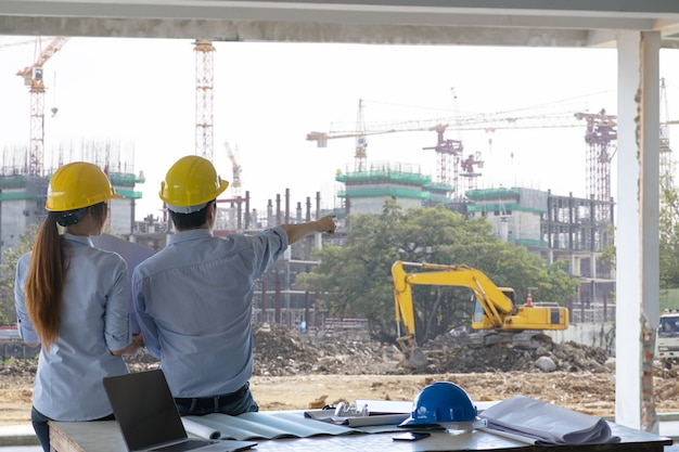 Ingenieur groep en werknemer vergadering, discussie met bouw blauwdruk op het terrein werk en wijsvinger op de werkplaats