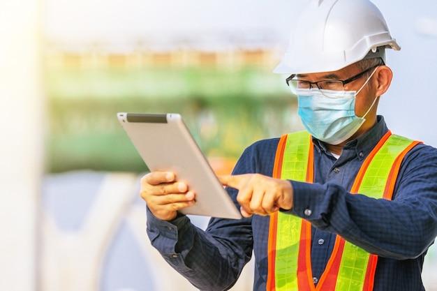 Ingenieur houdt tablet-werkplaatsconstructie vast