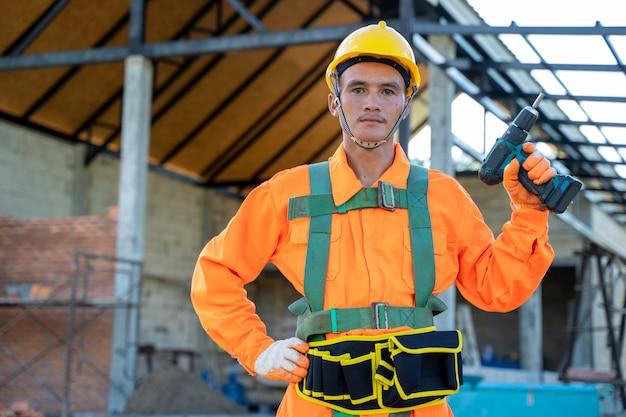 Ingenieur in beschermende uniform en beschermende helm op de bouwplaats