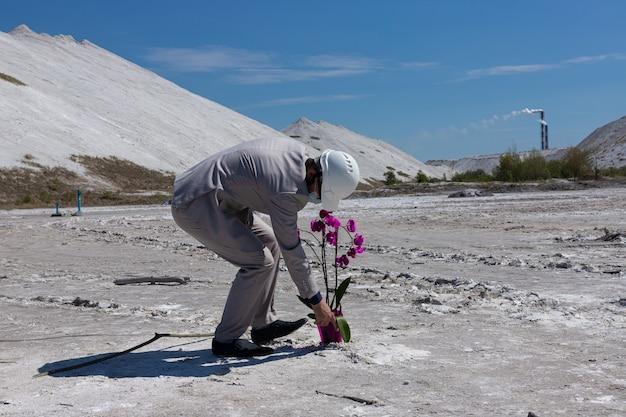 Ingenieur in een witte helm tegen de achtergrond van de industriële zone beschermt een orchideebloem. ecologisch concept van milieubescherming.