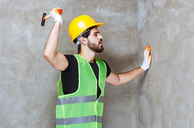 Ingenieur in gele helm en industriële handschoenen die de betonnen muur raken met een bijl