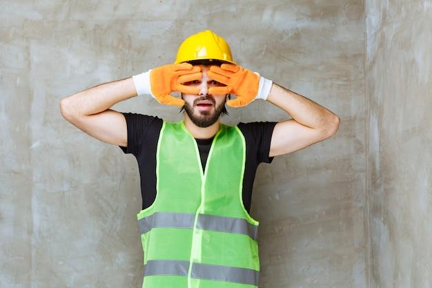 Ingenieur in gele helm en industriële handschoenen die over zijn vingers kijken