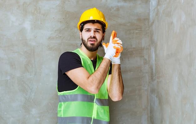 Ingenieur in gele helm en industriële handschoenen die pistoolteken in de hand tonen