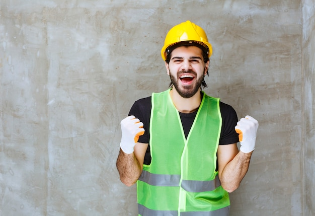 Ingenieur in gele helm en industriële handschoenen die tevredenheidsteken tonen