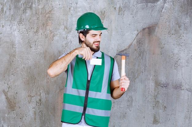 Ingenieur in gele uitrusting en helm die een houten behandelde bijl houdt en zijn visitekaartje voorstelt.