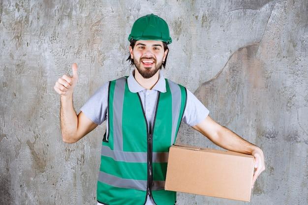 Ingenieur in gele uitrusting en helm die een kartonnen doos vasthoudt en een positief handteken toont