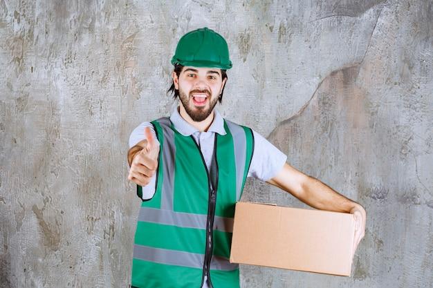 Ingenieur in gele uitrusting en helm die een kartonnen doos vasthoudt en een positief handteken toont.
