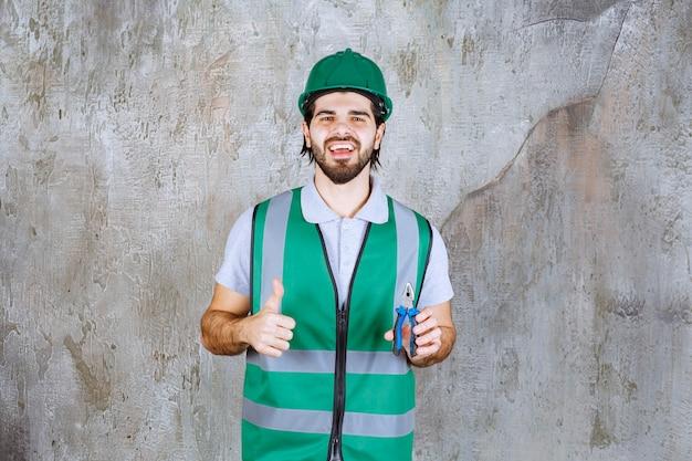 Ingenieur in gele uitrusting en helm die een tang vasthoudt en duim omhoog laat zien