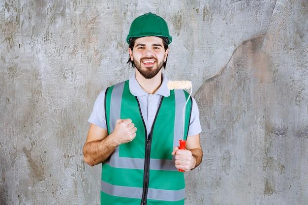Ingenieur in gele uitrusting en helm die een trimrol vasthoudt en een positief handteken toont