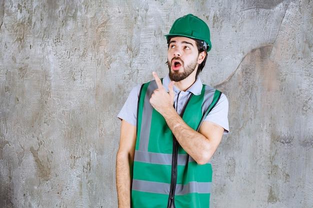 Ingenieur in gele uitrusting en helm die op betonnen muur staat en iets laat zien.