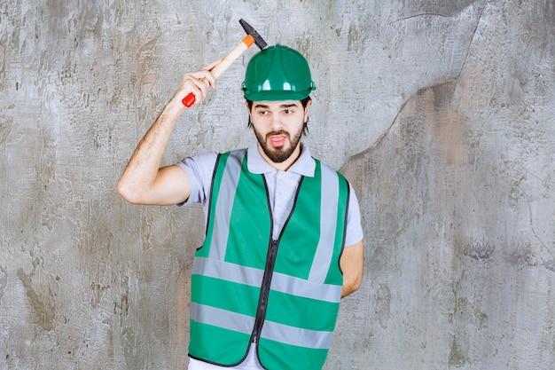 Ingenieur in gele uitrusting en helm met een houten bijl en ziet er verward uit.