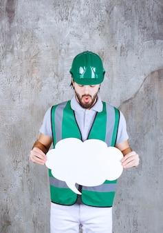 Ingenieur in gele uitrusting en helm met een infobord in de vorm van een wolk en ziet er attent en verward uit.
