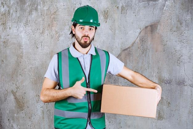 Ingenieur in gele uitrusting en helm met een kartonnen doos en ziet er verward en attent uit.