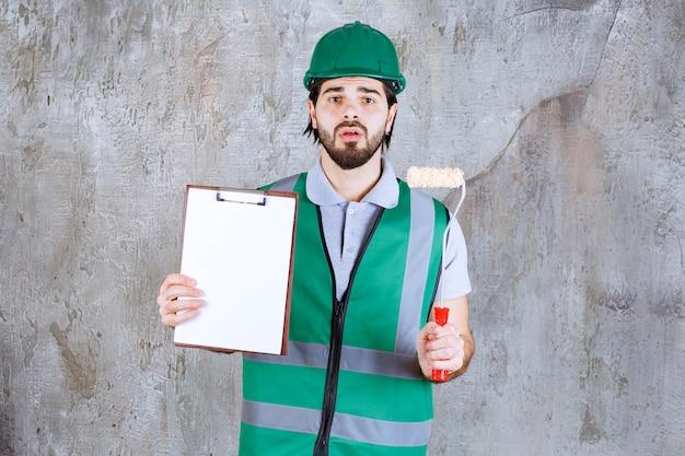 Ingenieur in gele uitrusting en helm met een trimrol en een vel papier en ziet er verward uit.
