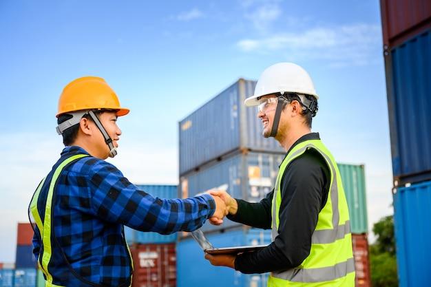 Ingenieur in gesprek met een jonge aziatische voorman die werkt in het transport- en logistiekconcept van de vrachtindustrie