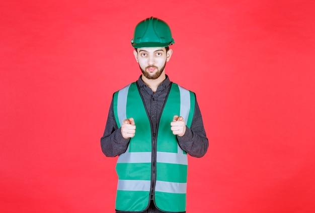 Ingenieur in groen uniform en helm die de persoon vooruit opmerkt.