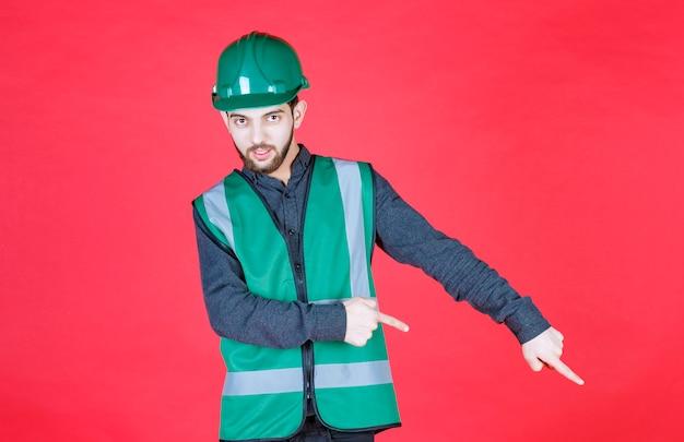 Ingenieur in groen uniform en helm die hieronder iets toont.