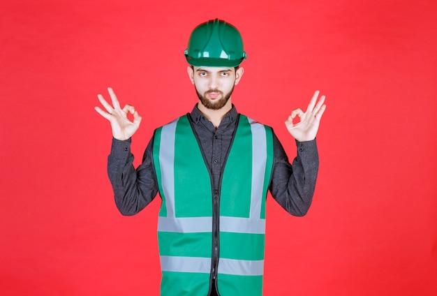 Ingenieur in groen uniform en helm die meditatie doet.
