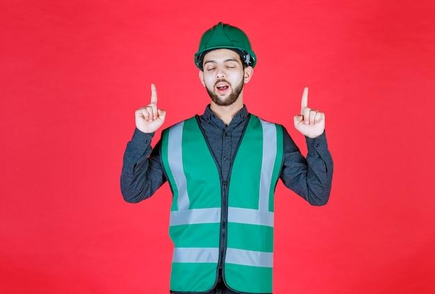 Ingenieur in groen uniform en helm die naar boven wijst.