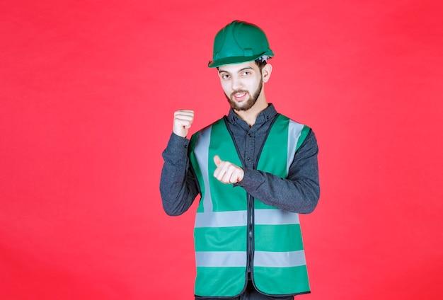 Ingenieur in groen uniform en helm die naar de achterkant wijst.