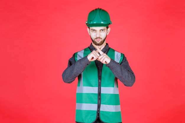 Ingenieur in groen uniform en helm die om stilte vraagt.