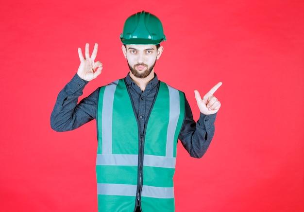 Ingenieur in groen uniform en helm die plezierteken tonen.