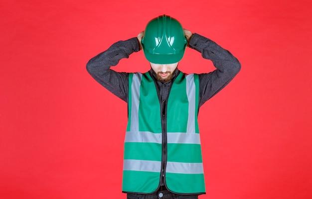 Ingenieur in groen uniform en helm die zijn hoofd vasthoudt terwijl hij moe is.