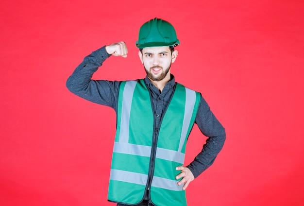 Ingenieur in groen uniform en helm die zijn vuist demonstreert.