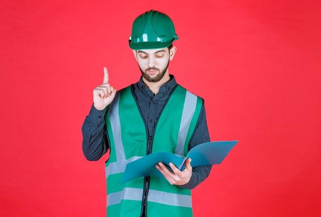Ingenieur in groen uniform en helm met een blauwe map, lezen en correcties aanbrengen.