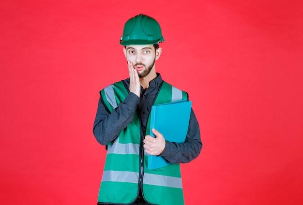 Ingenieur in groen uniform en helm met een blauwe map, ziet er doodsbang en opgewonden uit.