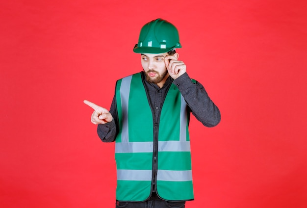 Ingenieur in groen uniform en helm met linkerkant.