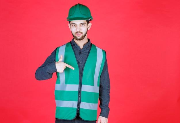 Ingenieur in groen uniform en helm wijzend op zichzelf.