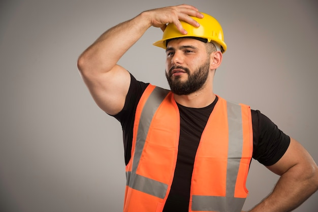 Ingenieur in oranje uniform gele helm dragen.
