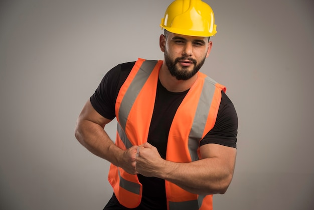 Ingenieur in oranje uniforme en gele helm met grote spieren.
