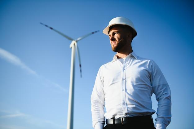 Ingenieur in tarweveld die de productie van turbines controleert