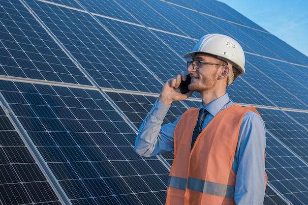 Ingenieur in uniform staande op een achtergrond van zonnepanelen. de zonnepark controleert de werking van het systeem, alternatieve energie om de energie van de wereld te besparen, fotovoltaïsche module idee voor schoon