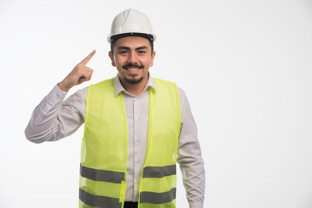 Ingenieur in uniform wijst naar zijn helm.