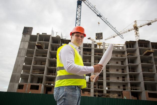 Ingenieur in veiligheidshelm die zich op bouwwerf bevindt en blauwdrukken controleert