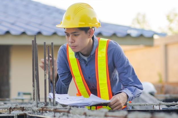 Ingenieur inspecteert op de bouwplaats bouwen
