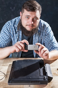 Ingenieur maakt shoot van laptop op telefooncamera. elektronische apparaten die technologie herstellen